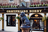 'Dog statue of Greyfriars Bobby in front of a bar; Edinburgh, Scotland'