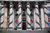 'A building with columns decorated with garland and wreaths at Christmas; Edinburgh, Scotland'