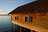 'A wooden building raised on pilings in a lake; Herrsching, Bavaria, Germany'