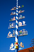 'Colourful images decorate a blue and white striped pole; Erling, Bavaria, Germany'