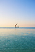 'A sailboat in the distance on the tranquil water of the Indian Ocean; Vamizi Island, Mozambique'