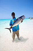 'A man stands in the shallow water holding a large fish; Vamizi Island, Mozambique'