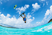 'Professional kiteboarder Jesse Richman kitesurfing over the crystal blue waters, Necker Island, British Virgin Islands'