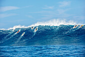 'Professional surfers paddling into large waves at the infamous big wave spot know as Jaws or Peahi, Maui, Hawaii, United States of America'