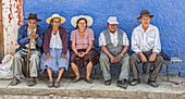 'A group of elderly Bolivian people sit on a bench watching a basketball game on a hot afternoon; Bolivia'