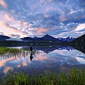 Man fly fishing on a quiet evening at Auke Lake, Juneau, Alaska.