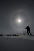 'Man snowshoeing along the Dempster Highway under a moon glowing with rings; Yukon, Canada'