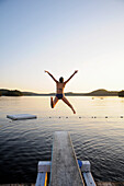 'A swimmer jumps off a diving board as the sun sets over a lake in Muskoka; Huntsville, Ontario, Canada'