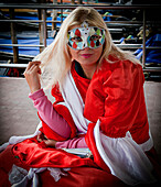 'A girl wearing a colourful eye mask; Venice, Italy'