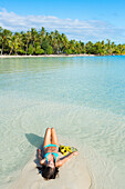 'Woman with snorkel gear laying on white sand in aqua blue water, Tahaa, French Polynesia'