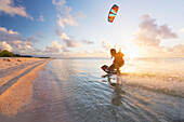 'Kiteboarding in tropical lagoon in the South Pacific at sunset, Tikehau, French Polynesia'