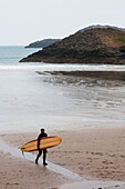 'Surfer coming out of the chilly winter waters heading to car park at Whitesands Beach on the Pembrokeshire Coast Path; Pembrokeshire, Wales'