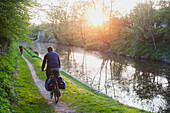 'Cyclist cycling along canal side at sunset; Wiltshire, England'