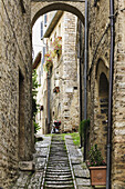'Stone buildings and cobblestone walkway under an arch; Spello, Umbria, Italy'