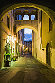 'Street between residential buildings illuminated with lights at dusk; Spoleto, Umbria, Italy'