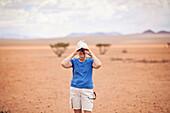 An older woman looks through binoculars while on safari in the Namib Desert, Namibia