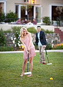 A young beautiful lady hit a croquet ball with a mallet, her male partner stands at a distance with a mallet in his hand observes her.