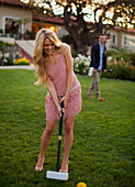 A beautiful young lady plays croquet, her male partner watches from behind.