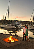 A young girl with a drink in her left hand stands intimately with her male partner next to a fireplace by the marina.