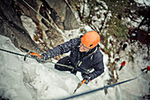 A male climber is sprayed with ice chunks while Ice climbing near Whistler, BC, Canada.