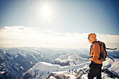 A mountaineer take in the view from a mountain summit in the Coquihalla Recreation Area of British Columbia, Canada.
