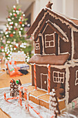 Homemade gingerbread house with Christmas Tree in the background.