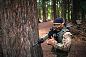 A man carries an automatic weapon while walking through the forest.