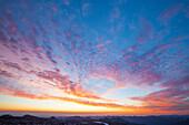 The sun illuminates the sky above Burroughs Mountain just before sunrise.