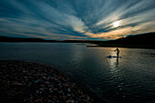 A man paddle boarding in the evening in Kittery, Maine.