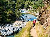 Jen Homan and Kavu trail running along the Yuba River at Yuba River State Park, Nevada County, California