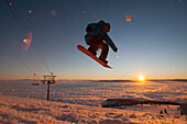 Snowboarder jumping at sunset in Whitefish, Montana.
