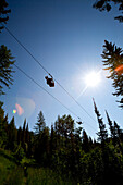 Two people ride a zip line in Whitefish, Montana.
