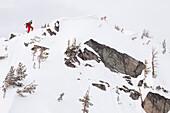 A male backcountry skier boot packs up a steep ridge to ski a line in the Beehive Basin near Big Sky, Montana.