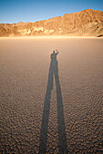 A person takes a photo of their shadow on the Racetrack Playa in California's Death Valley National Park.