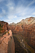A hiker stands on a cliff along the popular Angels Landing trail in Zion National Park near Springdal Utah.