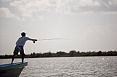 a fly fisherman casts his rod while standing on the bow of a boat with mangroves in the background