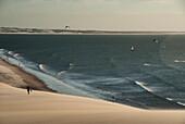 Girl in silhouette walking by dunes of Jericoacoara with a sea full of people kiteboarding in Brasil