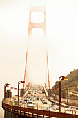 Front view of the Golden Gate with pedestrian and automobile traffic surrounded by fog.