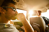 Portrait of a boy sitting in the back seat of a minivan is thoughtful, while the setting sun directly enters from the window while traveling in San Diego, California.