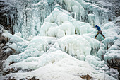 Man lead climbing an ice fall in the middle of a snow storm in Argenti?®re, Chamonix, France.
