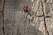 Man with red jacket, grey helmet and various climbing gear climbing a wall above Teton Village, near Corbet's Couloir, Jackson Hole, Wyoming.