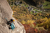 Climber belaying his partner from the top of a pitch in Cadarese with the village and the valley in background. Ossola, Italy.