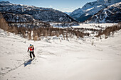 Girl with red jacket cross country skiing above Devero Valley. Baceno, Ossola, Italy.