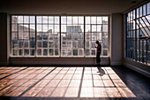 A woman standing in front of panel windows as the sun lights an open room