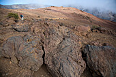 A woman in her thirties carrying an infant hikes in the high-elevation volcanic Haleakala crater, with ropy pahoehoe lava in the foreground.