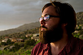 A man in his late twenties, takes in the view overlooking the city of Albuquerque, New Mexico.