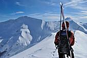 Male ski alpinist admiring mountain panorama.