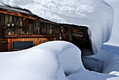 Old, rustic, wooden hous covered with snow.