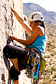 A female climber adjust a spring loaded camming device while working her way up Sidewinder (5.10b) in Joshua Tree National Park, California.