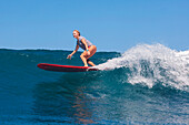 Picture of young woman surfing.